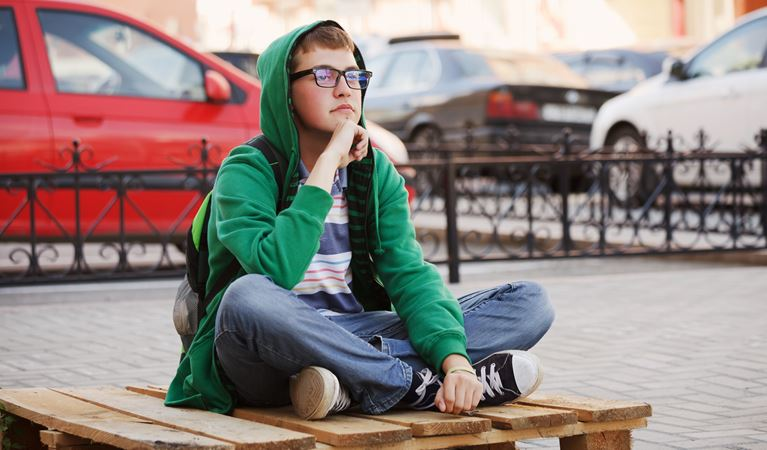 shutterstock 109966928%5b1%5d young boy sitting against a city traffic