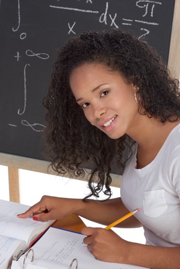 shutterstock 68817841%5b1%5d high school or college  female student sitting by the desk at math class  blackboard with advanced mathematical formals in background