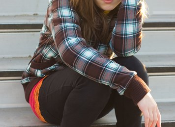 shutterstock 73695892%5b1%5d a teenage girl sitting on the bleacher steps with a serious expression